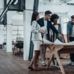 Group of young business people working together in creative office while standing near the wooden desk